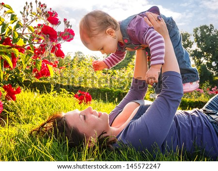 Happy young mother playing with little daughter in park - stock photo