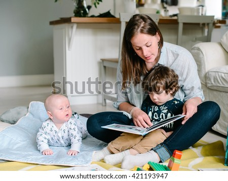 Happy young mother reading a book to their children sitting in the floor of the house. The concept of family - stock photo