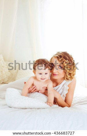 happy young mother rests with her son at home - stock photo