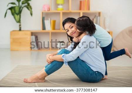 Happy young mother sitting on the floor when her daughter kissing her from behind - stock photo