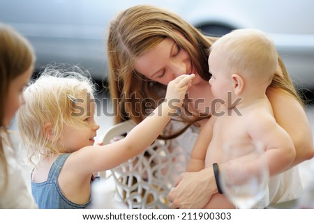 Happy young mother with children in a outdoors cafe - stock photo
