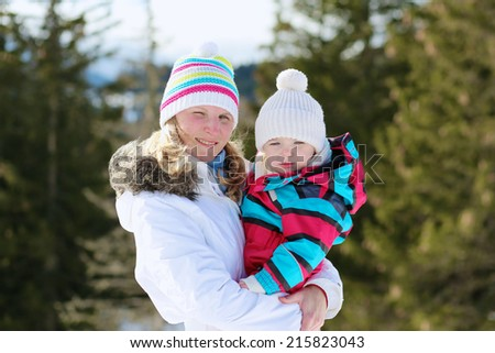 Happy young mother with cute toddler daughter in colorful snowsuit enjoying family vacation in snowy alpine village on a sunny winter day - stock photo