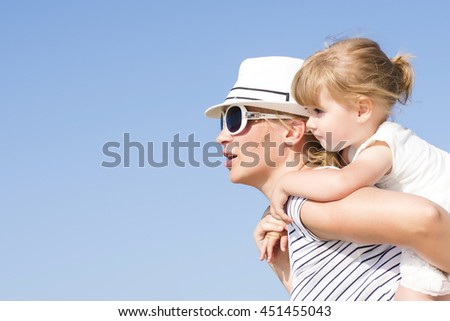 Happy young mother with hat and sunglasses holding daughter outdoor.  Happy family concept - stock photo