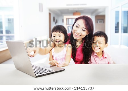 Happy young mother with her children using ultrabook laptop computer to enjoy entertainment at home - stock photo
