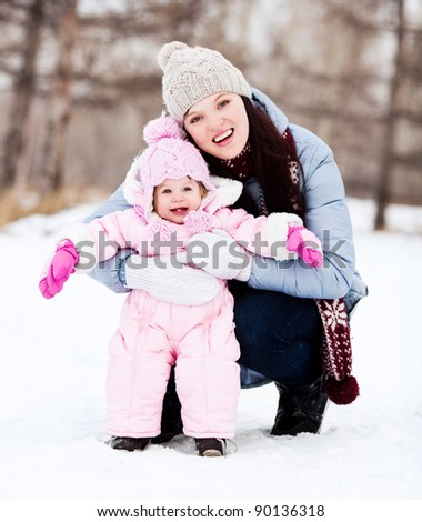 happy young mother with her daughter spending time outdoor in the winter park - stock photo