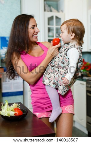 Happy young mother with little daughter in the house kitchen. - stock photo