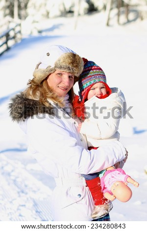 Happy young mother with toddler daughter in white warm jackets enjoying apres-ski during vacation in snowy alpine village - stock photo