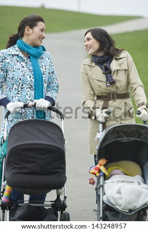 Happy young mothers pushing strollers in park having chat - stock photo