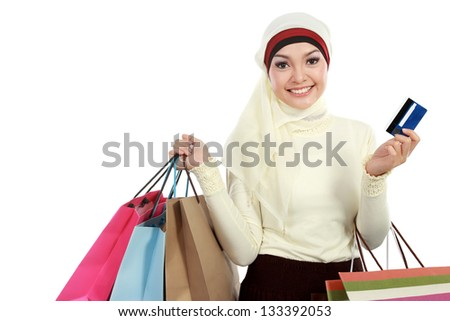 Happy young muslim woman in scarf with shopping bag and credit card - stock photo
