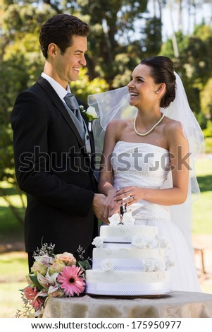Happy young newlywed couple cutting wedding cake at the park - stock photo