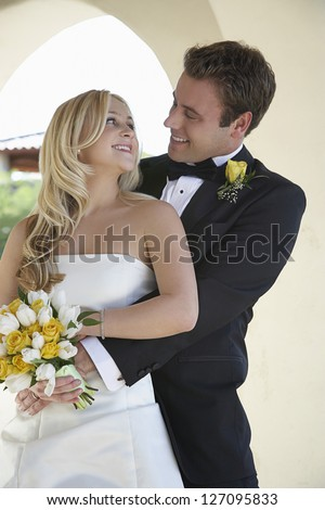 Happy young newlyweds embracing while looking at each other - stock photo