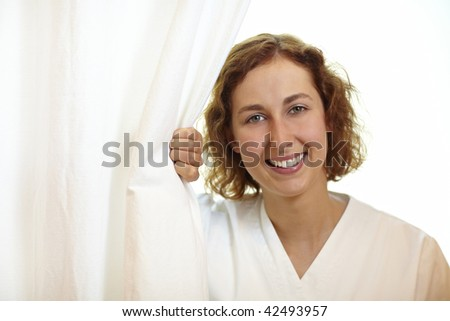 Happy young nurse pulling white curtain aside - stock photo