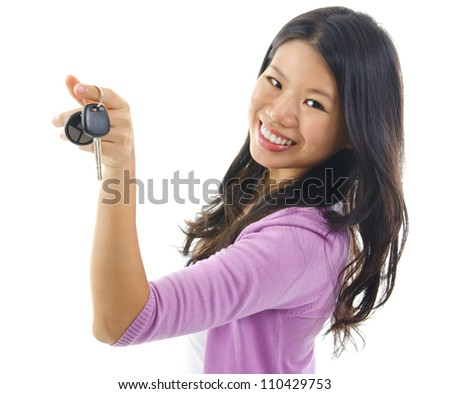 Happy Young pan asian woman showing her new car key, isolated on white, focus on car key - stock photo