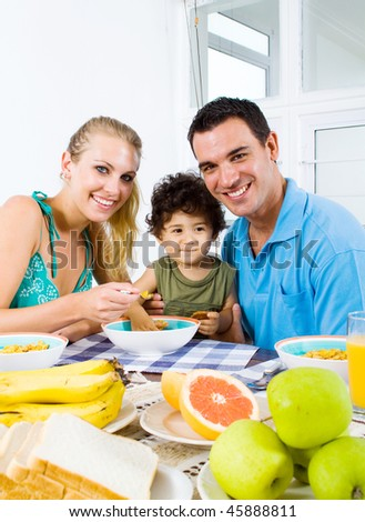 happy young parents and toddler boy at breakfast table - stock photo