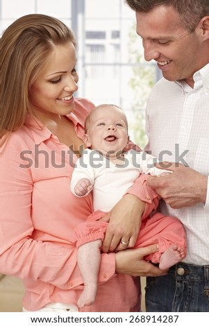 Happy young parents holding happy baby. - stock photo