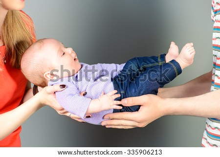 Happy young parents holding their adorable baby. Family concept. Care and safety. Studio shot. - stock photo