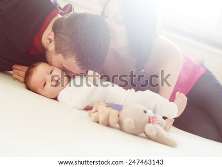 Happy young parents with their little baby girl at home - stock photo