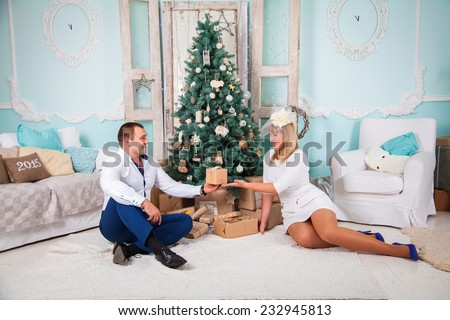 Happy young people are giving each other gifts near the Christmas tree. - stock photo