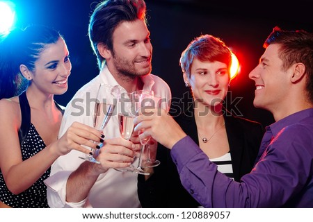Happy young people clinking with champagne in nightclub. - stock photo