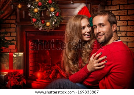 Happy young people give each other gifts by the fireplace near the Christmas tree. - stock photo