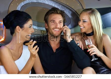 Happy young people having fun in luxury car, drinking, smoking cigar. - stock photo