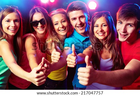 Happy young people show thumb up - stock photo