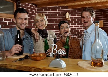 Happy young people standing at bar in pub, drinking beer, looking at camera, smiling.? - stock photo
