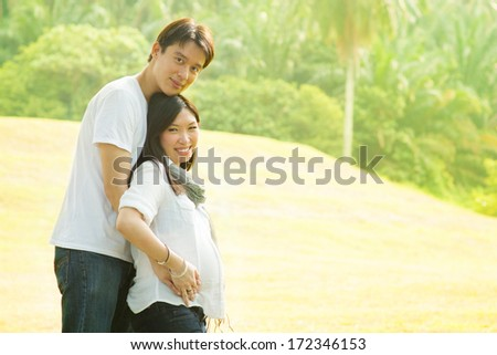 Happy young pregnant Asian couple. - stock photo