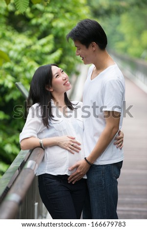 Happy young pregnant asian couple in the nature  - stock photo