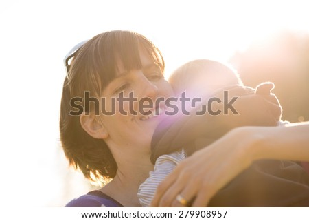 Happy young  protective mother lovingly cuddling her baby boy to her shoulder with maternal smile backlit by a bright sunburst. - stock photo