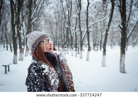 Happy young redhead woman having fun in the snow. - stock photo