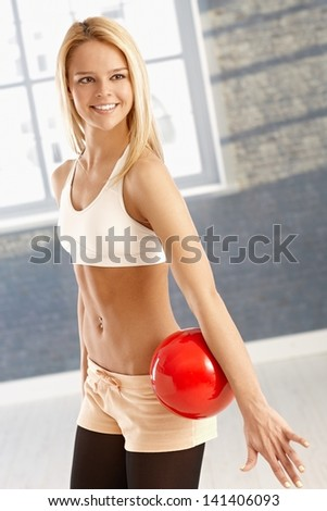 Happy young rhytmic gymnast exercising with ball. - stock photo