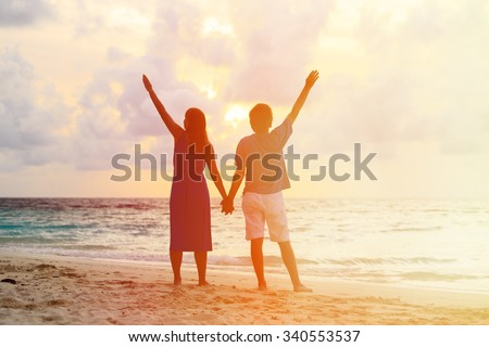 Happy young romantic couple on the beach at sunset - stock photo