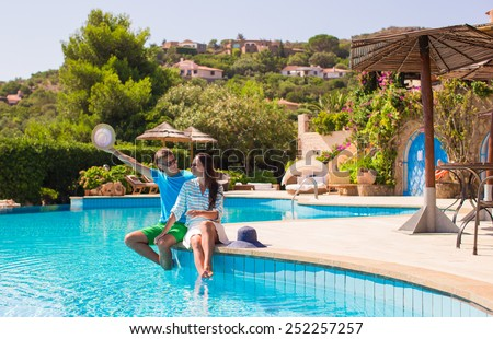Happy young romantic couple relaxing near swimming pool - stock photo