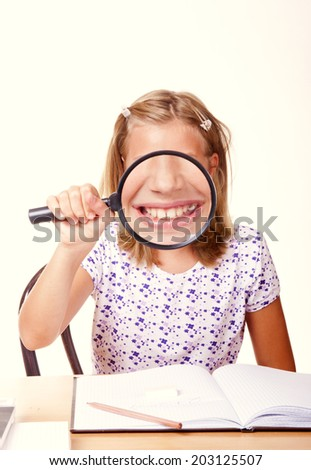 happy young school girl sit with a magnifying glass in hand and write homework/happy young school girl  - stock photo