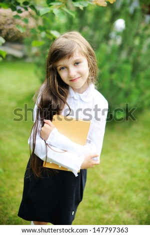 Happy young school girl with book - stock photo