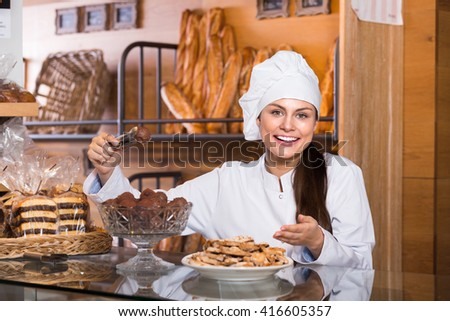 Happy young shopgirl working in bakery with bread and different pastry  - stock photo