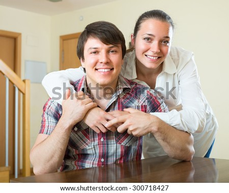 Happy young smiling couple hugging at home  - stock photo