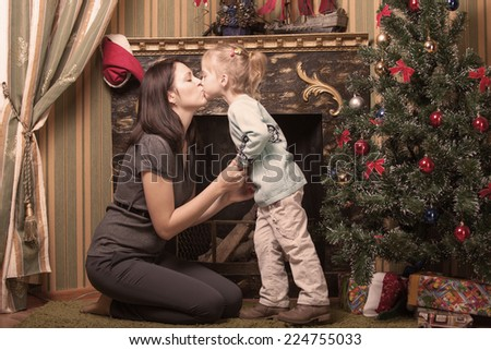 Happy young smiling family near the Christmas tree celebrate New Year. Mom and kid at Christmas tree. Mother and child on Christmas Eve. Mummy and Baby.  - stock photo