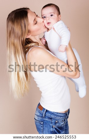 Happy young smiling mother with her little baby boy - stock photo