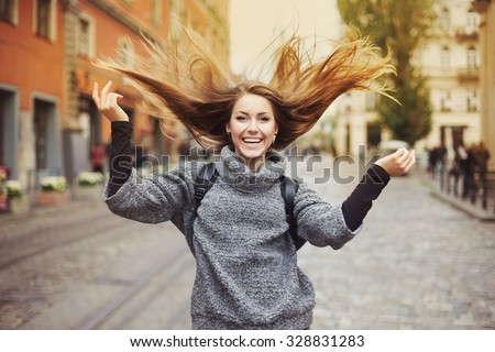 Happy young smiling woman playing with her long beautiful hair. Emotional portrait - stock photo