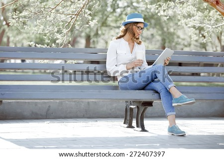 Happy young student with a tablet and a disposable coffee cup sitting on the bench and reading in a summer park. - stock photo