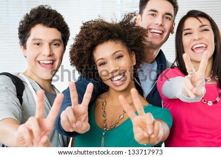 Happy Young students Showing Victory Sign - stock photo