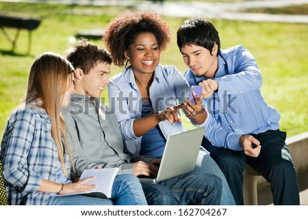 Happy young students with using mobilephone in university campus - stock photo