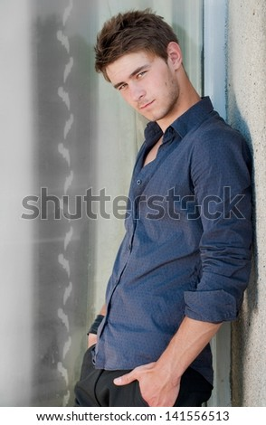 Happy young stylish man hands crossed looking in camera outdoors - stock photo