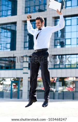 Happy young successful businessman jumping against office building - stock photo