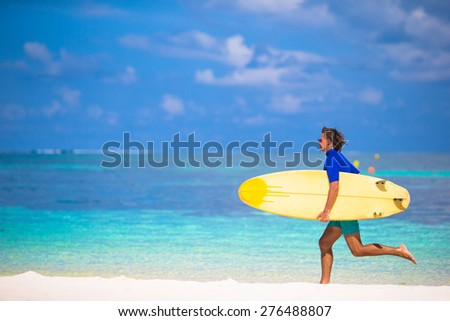Happy young surf man runing at the beach with a surfboard - stock photo