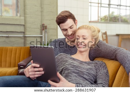 Happy Young Sweet Couple in Gray Shirts Sitting on the Sofa at the Living Area with Tablet Computer. - stock photo