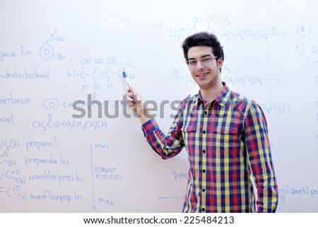 happy young teenage boy portrait in school on chemistry classes and library - stock photo