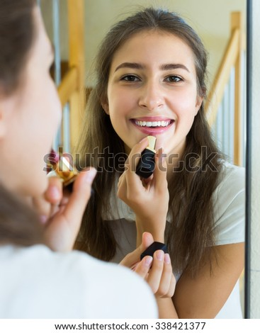 Happy young teenager applying lipstick in front of a mirror at home - stock photo